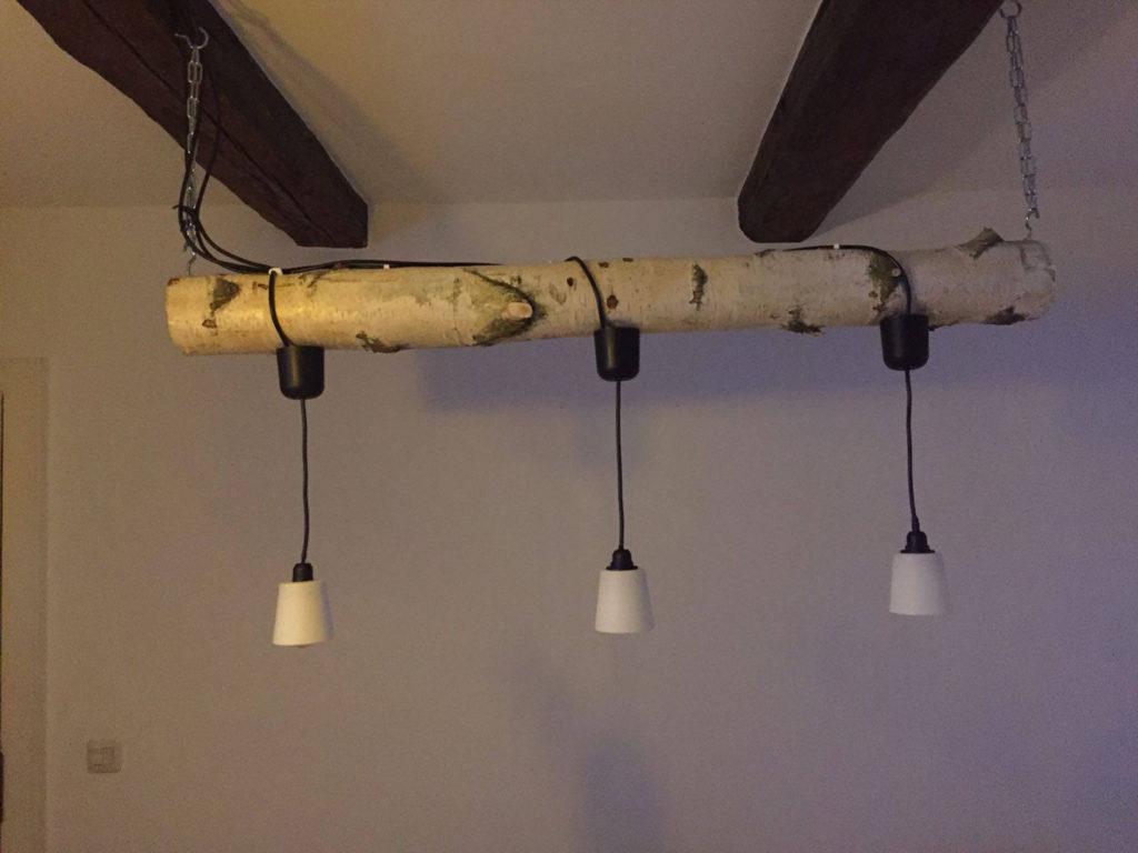 Birkenstamm als Lampenhalterung aufgehängt